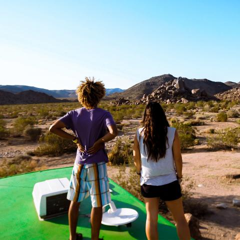 picture of two students on top of an RV, looking at a mountain