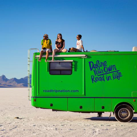 picture of three students on top of an RV in the desert