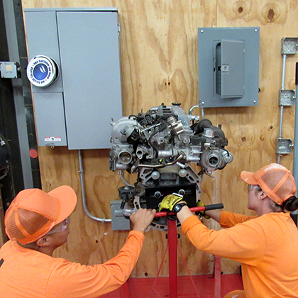 Incarcerated student working on car engine