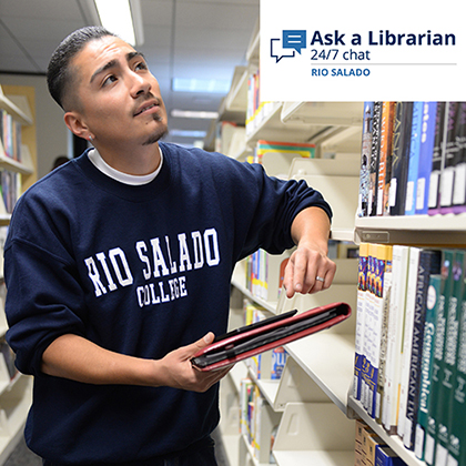 Student at library looking up at sign: Ask a Librarian 24/7 chat at Rio Salado.