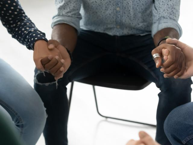 Up close view of three people holding hands as part of a therapy session.