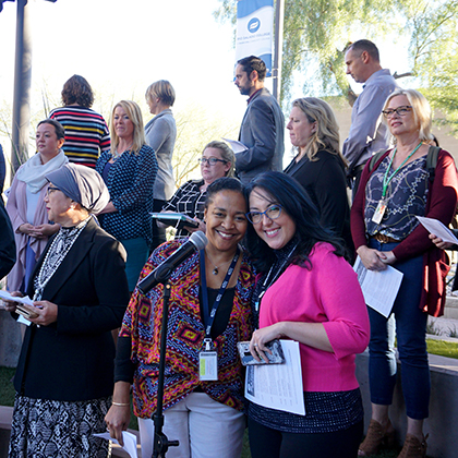 Rio Salado Employees gathered at an event, two attendees smiling at camera