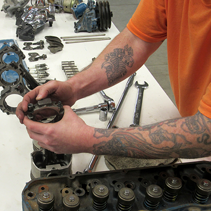 Incarcerated student working on automotive parts