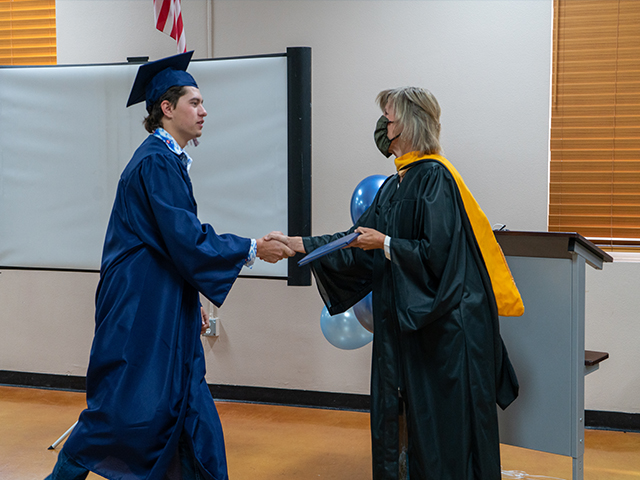 President Smith congratulates dual enrollment graduate at Heritage Academy watch party.
