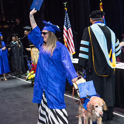 Fisher at the 2018 commencement ceremony with hertrusted companion Austin right by her side.