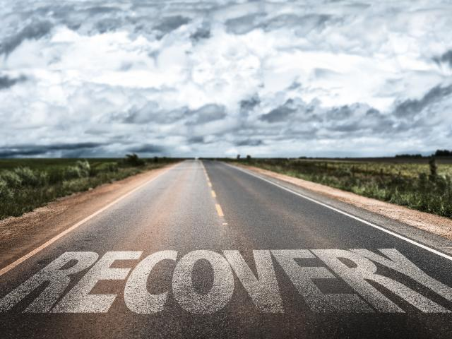 """Image of an empty rural highway with the word """"Recovery"""" over it. Cloudy skies in the distance."""
