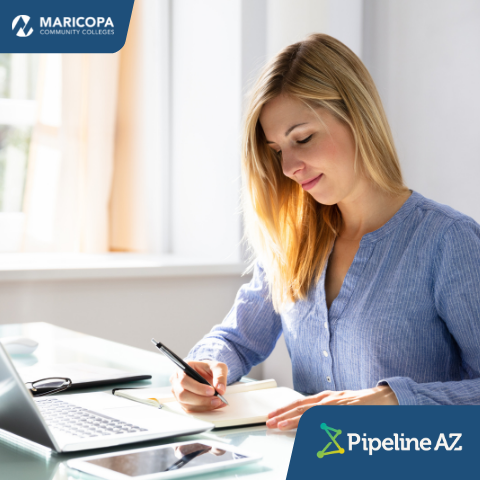 woman looking at paperwork in front of a laptop