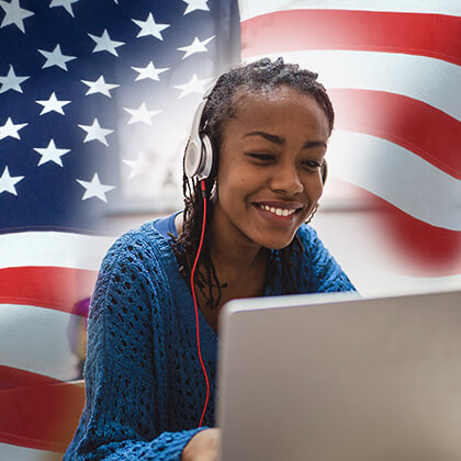 Young woman using laptop and headset, American flag in background