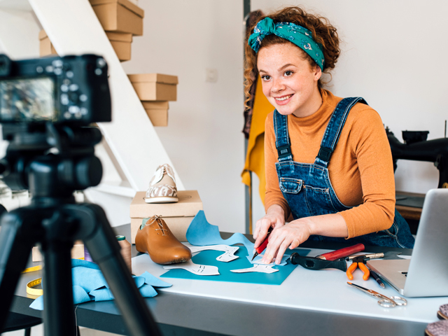 Young woman video recording how she makes shoes