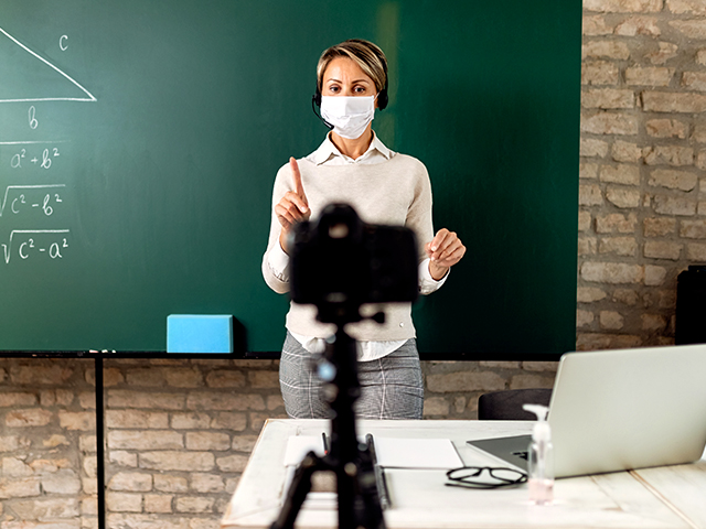 Teacher presenting in front of a chalkboard and video camera.