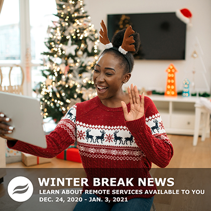 Young, black, female waving hello to IPad wearing classic ugly sweater and antlers, holiday furnishings in background.
