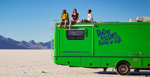 three people sitting on top of an RV in a desert setting