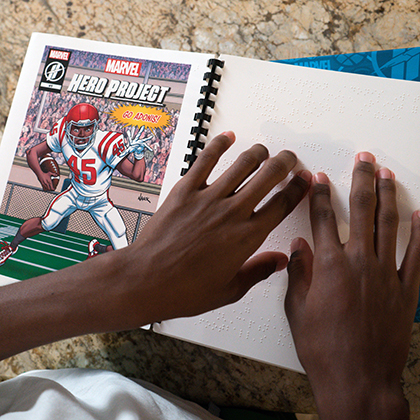 Photo of Adonis' hands reading the braille version of Unstoppable Adonis comic book, featuring an illustrated image of Adonis