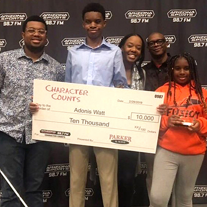Adonis with family holding a big check for $10,000 from Parker and Sons Character Counts scholarship fund.