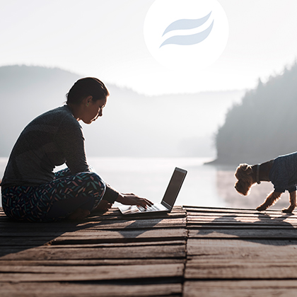 Young woman in her pajamas on a dock with her dog using laptop. Rio logo embedded in the sun.